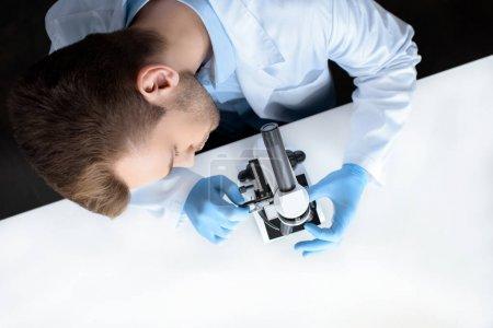 Photo pour Vue de dessus du scientifique travaillant au microscope en laboratoire - image libre de droit