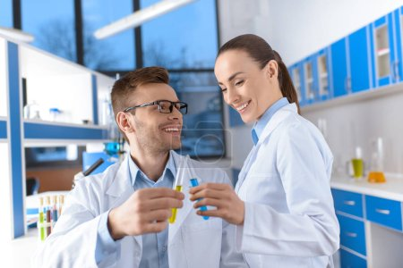 Photo for Portrait of smiling scientists in uniforms holding laboratory tubes - Royalty Free Image