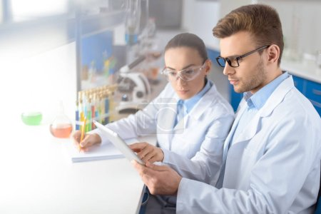Photo for Portrait of concentrated scientists using digital tablet during work in laboratory - Royalty Free Image