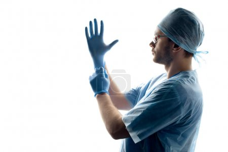 Photo pour Vue latérale du chirurgien en uniforme médical portant des gants sur blanc - image libre de droit