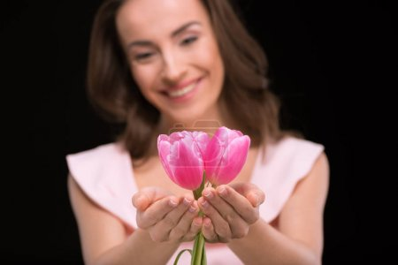Photo for Young smiling woman holding beautiful pink tulips  isolated on black, international womens day concept - Royalty Free Image