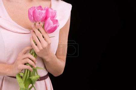 Photo for Close-up partial view of woman in dress holding pink tulips  isolated on black, international womens day concept - Royalty Free Image