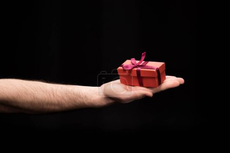 Photo for Partial view of man showing gift box in hand  isolated on black, international womens day concept - Royalty Free Image