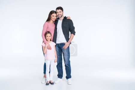 Photo for Happy young family with one child standing embracing and smiling at camera isolated on white - Royalty Free Image