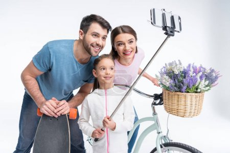 Photo for Portrait of smiling family with skateboard and bicycle making selfie isolated on white - Royalty Free Image