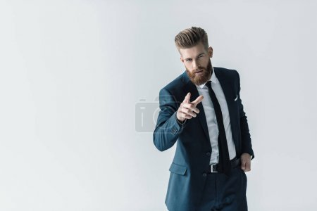 Foto de Handsome bearded businessman in stylish suit pointing at camera with finger isolated on grey - Imagen libre de derechos