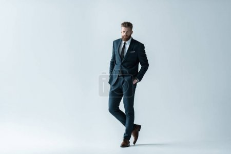 Foto de Confident bearded businessman in stylish suit standing with hands in pockets  isolated on grey - Imagen libre de derechos