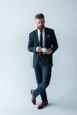 Photo pour Handsome bearded businessman in stylish suit holding coffee cup  isolated on grey - image libre de droit