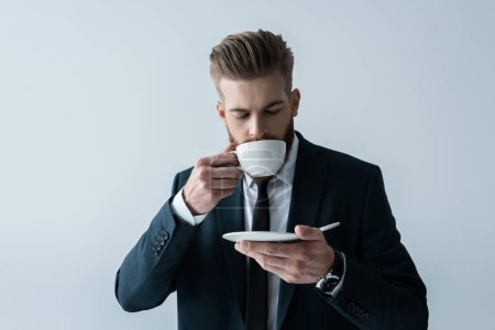 Photo for Handsome bearded businessman drinking coffee  isolated on grey - Royalty Free Image
