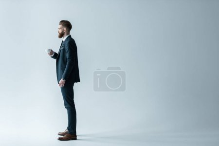 Photo for Side view of businessman in stylish suit holding coffee cup and looking away isolated on grey - Royalty Free Image