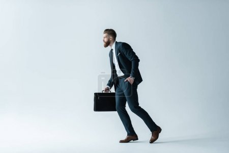 Photo for Side view of handsome bearded businessman running with briefcase  isolated on grey - Royalty Free Image