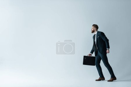 Photo for Side view of stylish bearded businessman running with briefcase  isolated on grey - Royalty Free Image