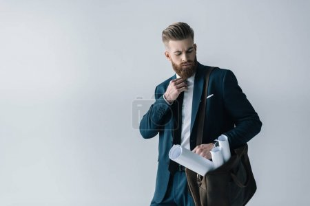 Photo for Young bearded businessman with blueprints in shoulder bag adjusting tie isolated on grey - Royalty Free Image