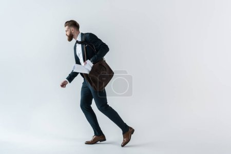 Photo for Bearded young businessman with blueprints in shoulder bag running  isolated on grey - Royalty Free Image