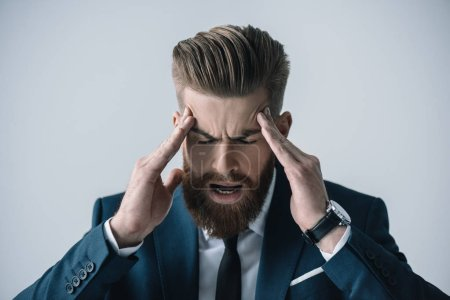 Photo for Stressed young bearded businessman with headache  isolated on grey - Royalty Free Image