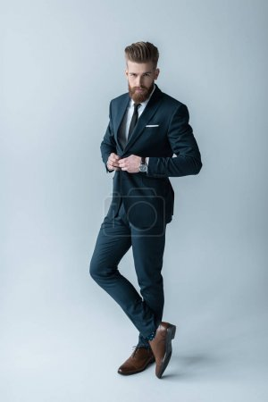 Foto de Handsome bearded businessman in trendy suit posing  isolated on grey - Imagen libre de derechos