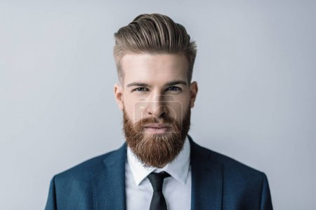 Photo for Stylish handsome bearded businessman looking at camera  isolated on grey - Royalty Free Image