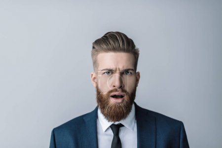 Photo for Shocked bearded businessman with open mouth looking at camera isolated on grey - Royalty Free Image