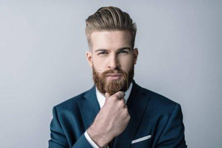 Photo for Stylish bearded businessman with hand on chin looking at camera isolated on grey - Royalty Free Image