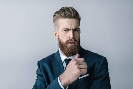 Photo for Stylish bearded businessman frowning and looking at camera isolated on grey - Royalty Free Image