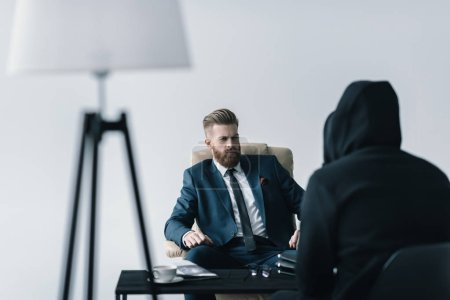 Photo pour Young bearded businessman talking with anonymous person in black hood on grey - image libre de droit