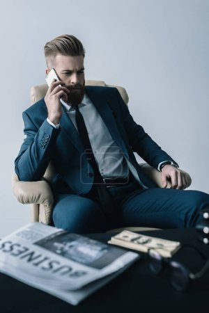 Foto de Portrait of focused businessman talking on smartphone  isolated on grey - Imagen libre de derechos
