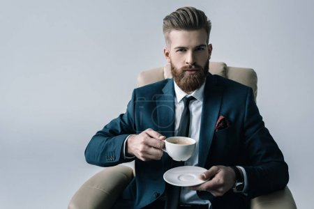 Photo pour Portrait of confident businessman in armchair holding cup of coffee isolated on grey - image libre de droit