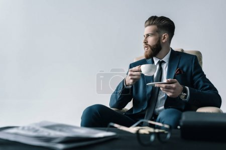 Foto de Portrait of elegant businessman holding cup of coffee  isolated on grey - Imagen libre de derechos