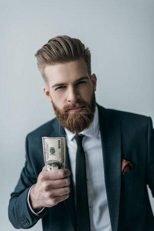 Photo pour Portrait d'un homme d'affaires élégant tenant des billets en dollars isolés sur du gris - image libre de droit
