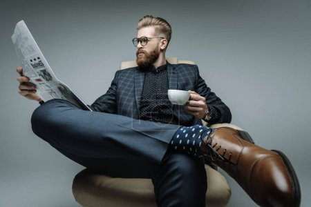 stylish businessman sitting in armchair