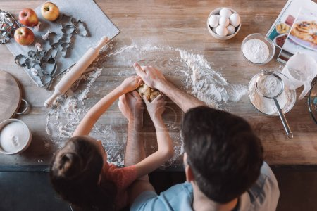 Photo for Overhead view of father and daughter kneading dough at kitchen table - Royalty Free Image