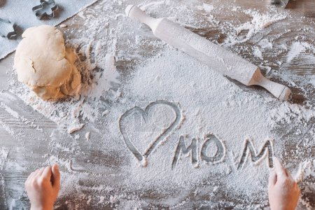 Photo for Partial top view of child drawing heart symbol and word mom in flour on table, Mothers day concept - Royalty Free Image