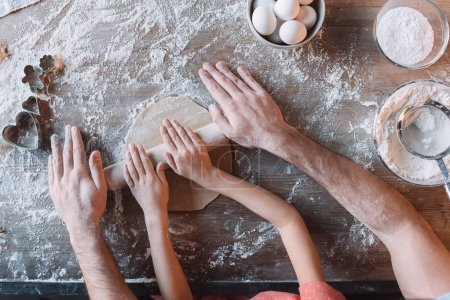 Photo for Partial top view of father and daughter kneading dough together - Royalty Free Image