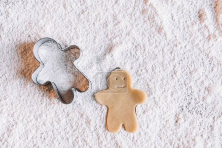 Photo for Close-up view of uncooked gingerbread man and cookie cutter on flour - Royalty Free Image