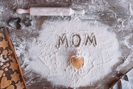 Photo for Top view of uncooked heart shaped cookie and word mom written in flour, Mothers day concept - Royalty Free Image