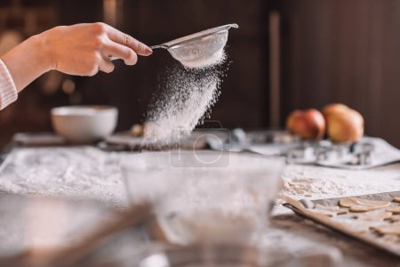Photo for Close-up partial view of human hand sifting flour above kitchen table - Royalty Free Image