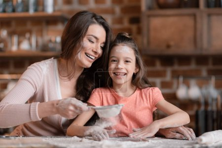 Photo for Happy mother and daughter with flour on faces sifting flour at kitchen table - Royalty Free Image