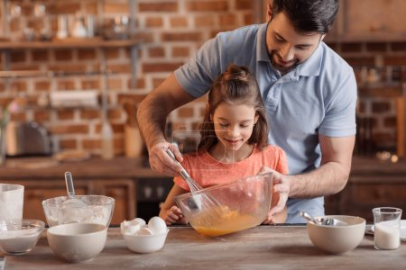 Photo for Portrait of father and daughter making cookies in kitchen - Royalty Free Image