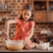 Girl sitting on table and mixing ingredients for d...
