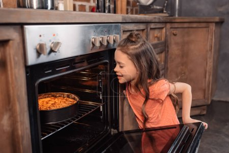Girl with cake in oven
