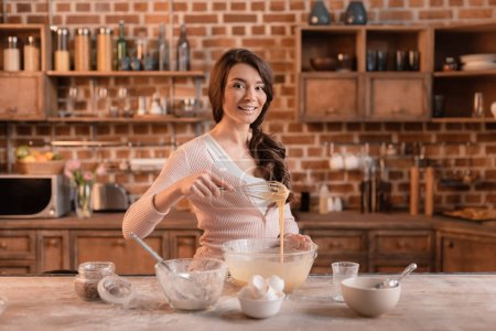 Photo for Portrait of smiling woman mixing ingredients for cake - Royalty Free Image
