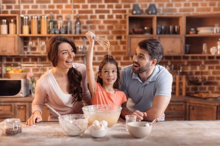 Photo for Portrait of happy family making cake together in kitchen - Royalty Free Image