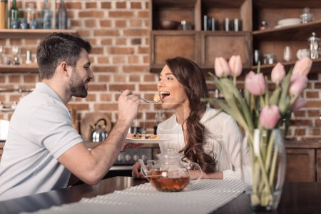 Photo for Side view of smiling man feeding woman with cake in kitchen - Royalty Free Image