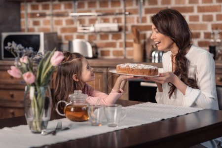 Photo for Side view of smiling mother and daughter holding cake in kitchen, mother's day holiday concept - Royalty Free Image