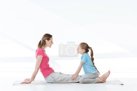 Photo pour Vue latérale de la mère et de la fille heureuses assises sur un tapis de yoga et se regardant - image libre de droit