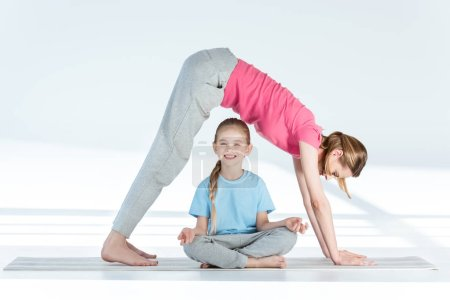 Photo for Mother practicing yoga above smiling daughter sitting in lotus position - Royalty Free Image