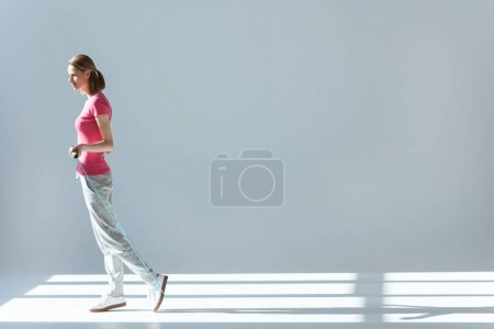 Photo for Side view of sporty woman standing with skipping rope in hands - Royalty Free Image