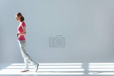 Photo pour Vue latérale de la femme sportive debout avec corde à sauter dans les mains - image libre de droit