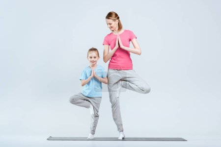 Photo pour Smiling sporty mother and daughter practicing yoga together, Vrikshasana yoga pose or tree pose  isolated on white - image libre de droit