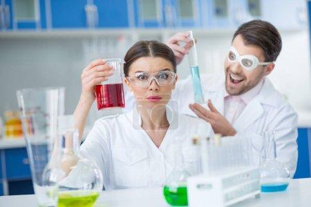 Photo pour Scientifiques excités hommes et femmes dans des lunettes de protection travaillant avec des réactifs en laboratoire - image libre de droit